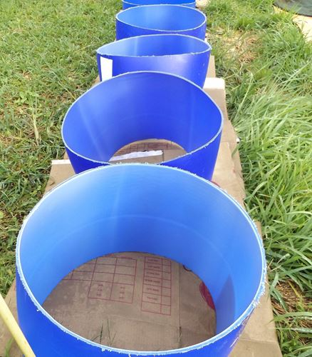row of half barrels with no bottoms, sitting on layer of cardboard